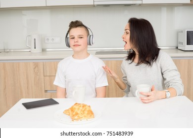 Mother scolds her son while he listening music and doesn't listen. Copcept of family conflict