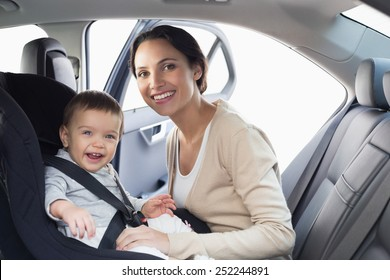 Mother securing her baby in the car seat in her car