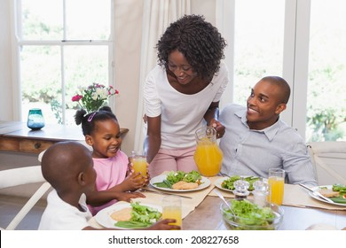 Mother serving juice to her family at lunch at home in the kitchen