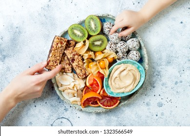 Mother sharing healthy vegan dessert snacks with toddler child. Concept of healthy sweets for children. Protein granola bars, homemade raw energy balls, cashew butter, toasted coconut chips