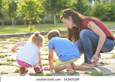 Mother and shildren drawing with chalk outdors