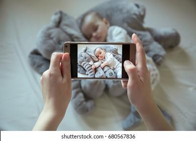 Mother shootin her sleeping newborn baby by smartphone