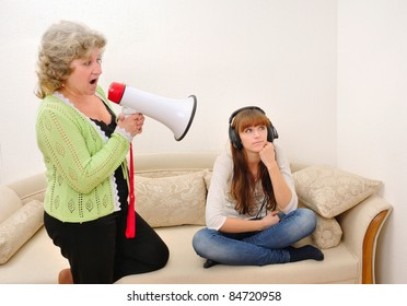 mother shouting at her daughter with a megaphone while she indifferently listens to music