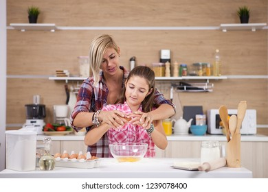 Mother showing daughter how to cook in domestic kitchen. Food preparation.