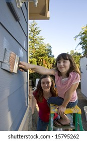 Mother showing her daughter where to apply paint as they paint their house. Vertically framed photograph.