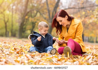 Mother showing yellow leaf to child in the park