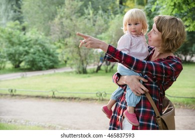 Mother shows daughter something interesting at the left side.
