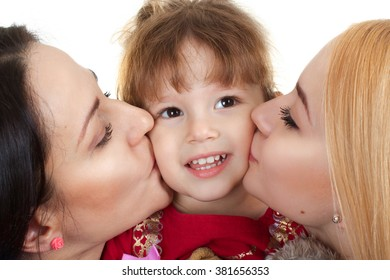 Mother and sister kiss on the cheek of a little girl isolated on white background