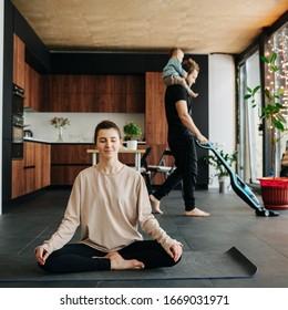 Mutter sitzt an leicht vereinfachter Lotus-Pose. Sie ist entspannt mit geschlossenen Augen, während der Vater Staubsauger Wohnboden mit ihrem kleinen Baby Reiten auf dem Nacken