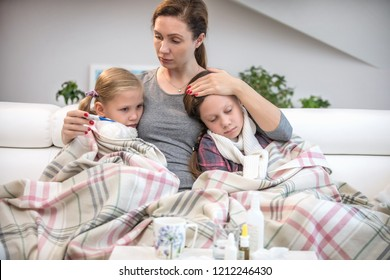 mother sits on the couch with 2 sick daughters and measures the temperature