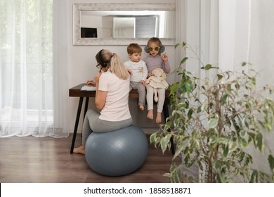 Mother sits on a fitness ball in headphones and works at home with her children during quarantine