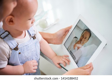 Mother sitting with baby on laps and video calling her husband via tablet computer