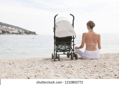 Mother sitting at the beach with a baby stroller, back view, seasonal affective disorder or postpartum depression concept