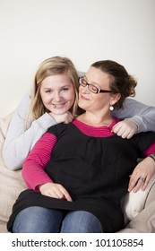 Mother sitting in a couch being hugged by happy teenage daughter. Mother is looking to her daughter, daughter is looking happily into the camera.