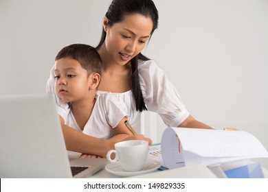 Mother sitting with her child and working at the same time