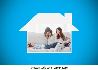 Mother sitting with her children on sofa against blue background with vignette