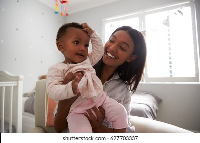 Mother Sitting In Nursery With Baby Daughter