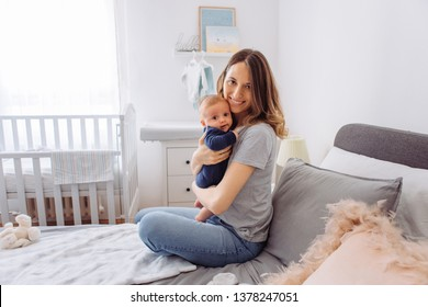 Mother sitting on bed and holding baby son in arms, they share moment of love