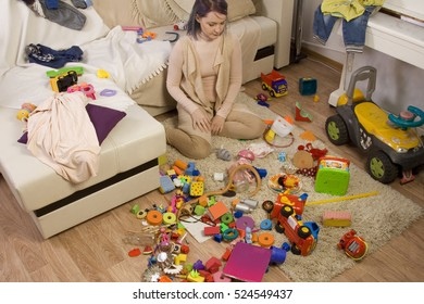 Mother sitting on the couch. Mom tired to tidy up the house. Child scattered toys. Children's room. Mess in the house