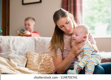 Mother sitting on the edge of the sofa in the living room and burping her newborn child after feeding him. Her other son is stadning behind the sofa playing while his toys.