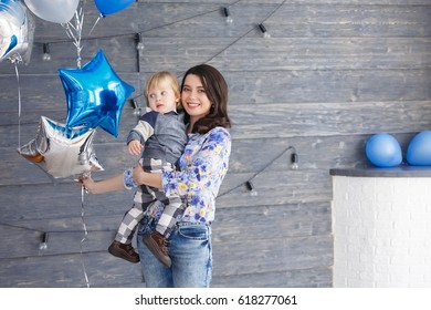 Mother sitting on the floor with her child and having fun. Mom with two years old baby boy spending time together.