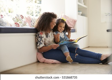 Mother sitting on the floor reading a book with her daughter