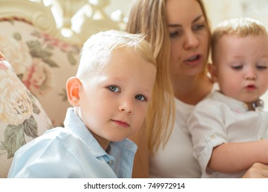 Mother Sitting on Sofa at Home with Two Sons