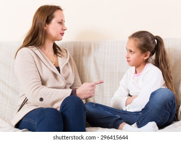 Mother sitting on sofa and scolding little daughter