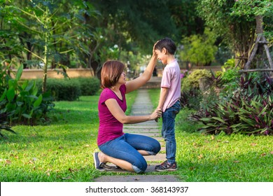 Mother sitting at park holding hands and teaching her son