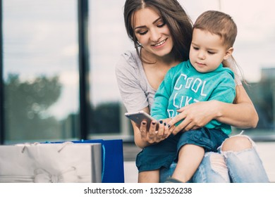 Mother sitting with son and using phone with packages near mall after shopping.