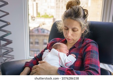 Mother with sleeping baby boy at home