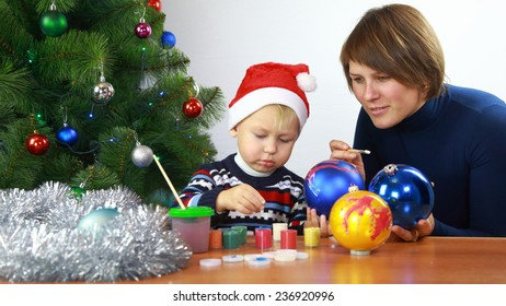 mother with small boy paint christmas balls
