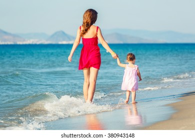 Mother and small daughter enjoy sea beach
