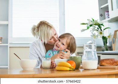 Mother and small daughter having breakfast in kitchen