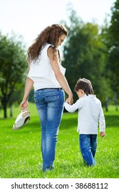 Mother with the small son barefoot walk on a summer grass in park