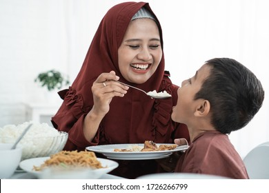 mother smile when feeding her son. Asian family enjoy eating together when breake fasting at home
