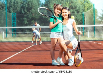 Mother smiling broadly. Mother smiling broadly before playing tennis with her lovely beaming daughter