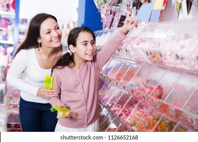 Mother with smiling girl choosing fruit jelly in the candy shop