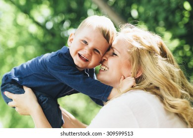 Mother smiling laughing and playing with her child outdoors on a nice summer day