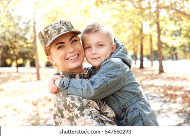Mother soldier and little kid embracing in the park