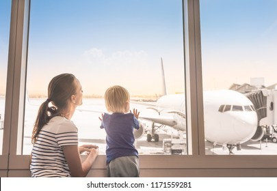 Mother and son at airport boarding terminal looking out window at airplane. Family travel and adventure.