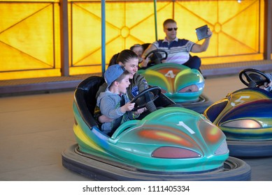 Mother and son in amusement park ride on car