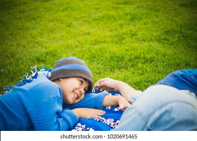Mother and son of Asian Relaxing on the outdoor fabric in the garden.