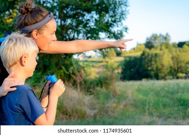 mother and son are birdwatching while hiking in countryside.