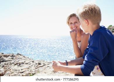 Mother and son bonding together, contemplating the sea on sunny holiday destination beach, talking conversation, smiling happy outdoors. Family mum and teenager enjoying travel recreation lifestyle.