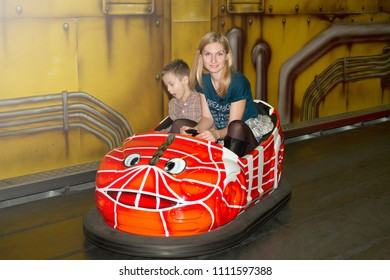 Mother and son in bumper car in amusement park. Woman and boy driving autoscooter