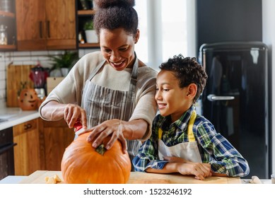 Mother and son carving pumpkin making Jack-o-Lantern
