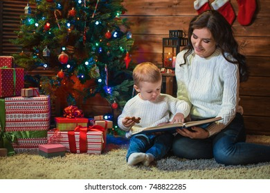 Mother and son celebrate Christmas in a decorated house with a Christmas tree and read the book