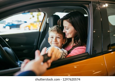 Mother and son choosing a new car to buy at the car showroom.