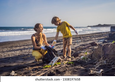 Mother and son are cleaning up the beach. Natural education of children